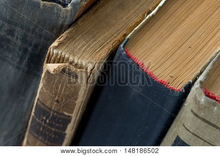 Different vintage antiquarian tattered books close up. Selective focus