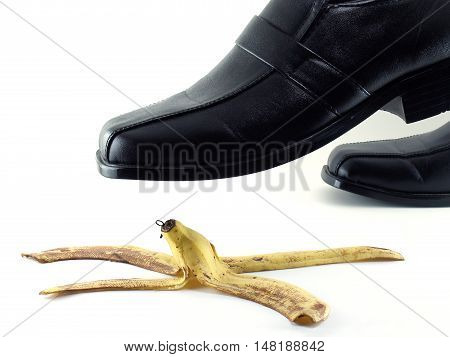 businessman's shoes (black leather shoes) stepped on a banana peel isolated on white background, beware slip and have an accident