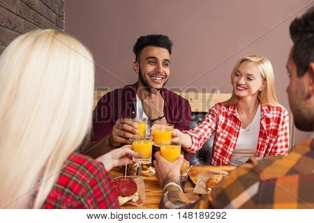 Young People Group Man And Woman Sitting In Burger Cafe, Toasting Orange Juice Order Fast Food On Wooden Table, Happy Smiling Fiends Meeting