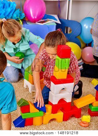 Group children game blocks on floor in primary school . Top view of primary school.