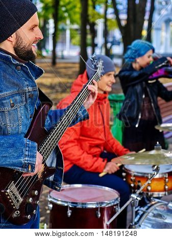 Group of music street performers with girl violinist on autumn outdoor. Music people play drums.