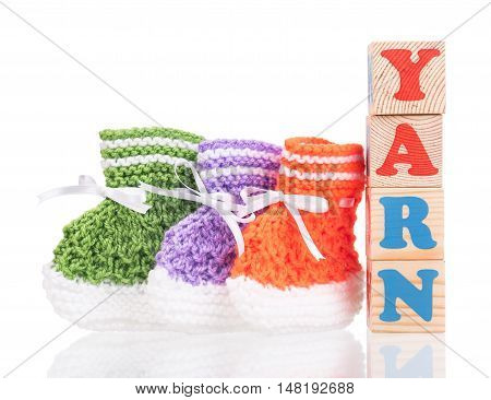 Bright cute little bootee with playing cubes isolated over white background