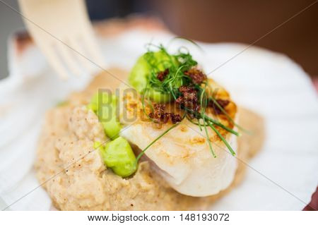 food, cooking and eating concept - close up of scallop snack with garnish