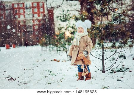 cute baby girl enjoying Christmas day outdoor in snowy park walking with decorations in warm outfit