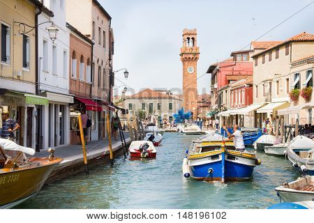 MURANO, ITALY - AUGUST 4, 2016: Tourists walking by a canal. The island located in the north of Venice is famous for its high-quality glass making.