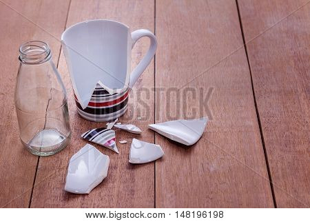 Broken cup on wooden background Vintage style