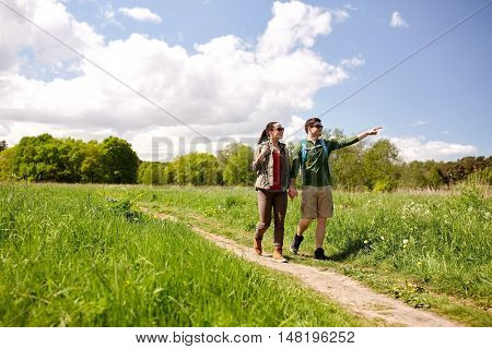 travel, hiking, backpacking, tourism and people concept - happy couple with backpacks holding hands and walking along country road