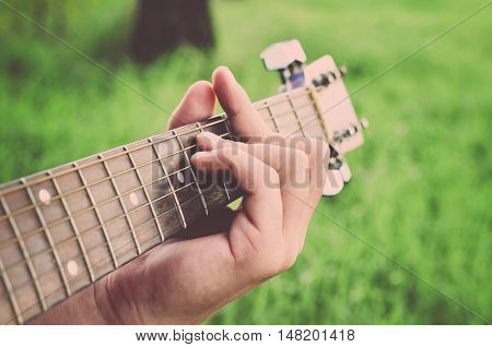 Man plays chords. Men's fingers and guitar strings (vintage)