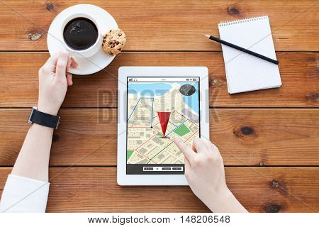 technology, navigation, location and people concept - close up of woman with gps navigator map on tablet pc computer screen, notebook and coffee on wooden table