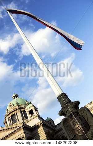 House of the National Assembly of Serbia in Belgrade with serbian flag in the wind