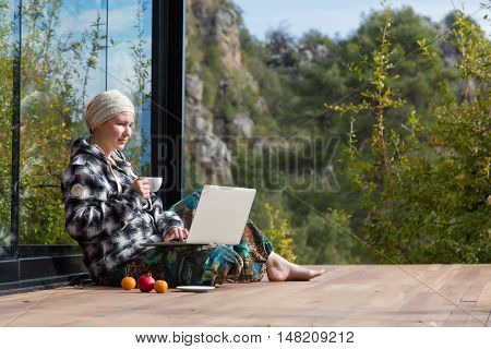 Cute Woman sitting on Terrace of Wooden Cabin drinking Coffee working on Computer fruits dropped aside large Window and Forest Mountains Background