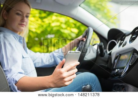 Woman In Car Texting On Mobile Phone Whilst Driving