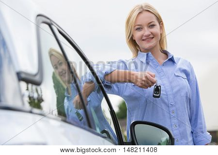 Young Female Driver Holding Car Keys Next To Vehicle