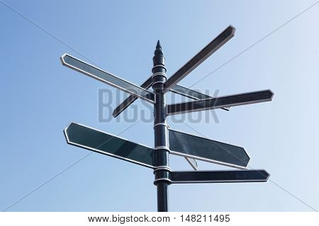 Signpost Pointing In Many Directions Against Blue Sky