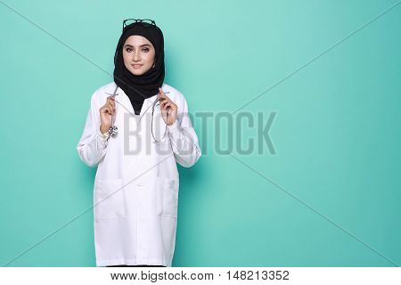 muslimah doctor holding a stethoscope isolated in turquoise background