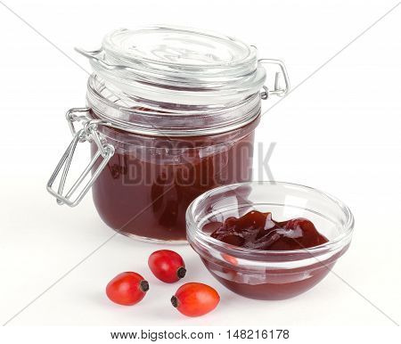 Rose hip jam and fruits over white, also rose haw or rose hep. Marmelade in a glass jar and bowl. Shells of red ripe fruits can be eaten raw and are one of the richest vitamin C sources in plants.
