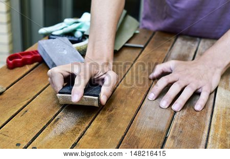 closeup of a young caucasian man sanding an old wooden table with a sanding block