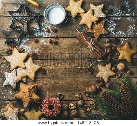 Christmas or new year background. Star shaped gingerbread cookies with sugar powder, nuts, cinnamon, anise, decorative rope, fir tree branch, pine cones on wooden background, top view, copy space