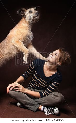 Beautiful Young Woman With A Funny Shaggy Dog On A Dark Background. High Quality, Photographed In Th