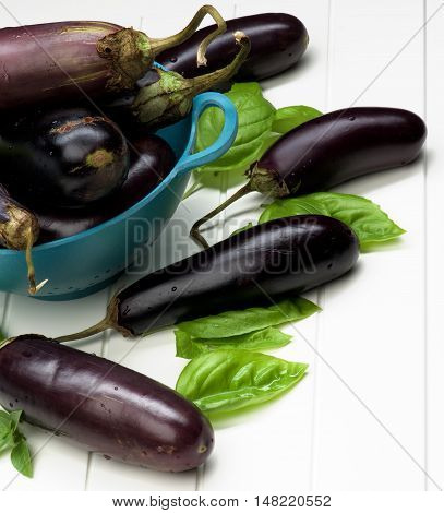 Heap of Fresh Raw Small Eggplants with Basil Leafs in Blue Colander closeup on White Plank background
