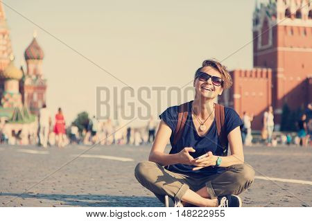 Young Attractive Woman Traveler With Backpack And Mobile Phone On The Background Of The Kremlin, Mos