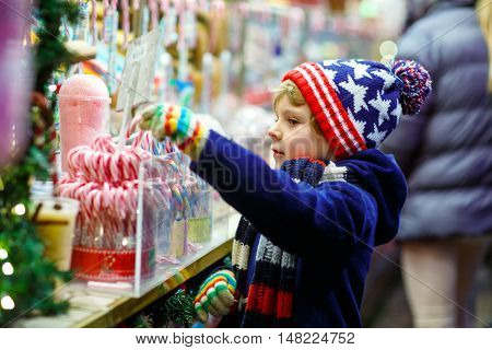 Little cute kid boy near sweet stand with candy canes. Happy child on Christmas market in Germany. Traditional leisure for families on xmas