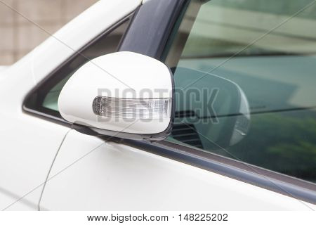 Side rear-view mirror closed for safety at car park.