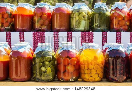 Zaporizhia/Ukraine- September  17, 2016: Family festival of homemade pickled canned vegetables and preserves. Variety of preserved fruits and vegetables -  tomatoes, cucumbers, zucchini, apricots and cherries  in  jars  outdoor exhibition.