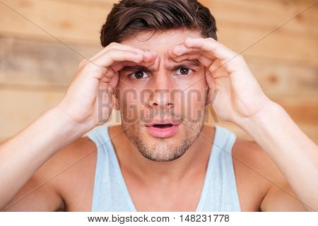 Close up of a man looking forward with his hand to his forehead over wooden background