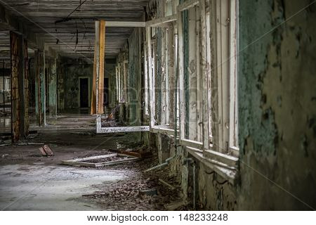 gloomy view of abandoned ruined hall with broken windows in Pripyat school