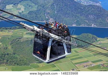 Mt. Stanserhorn, Switzerland - 7 May, 2016: people in a gondola of the Stanserhorn Cabrio cable car. Stanserhorn Cabrio is the the world's first double deck open top cable car, it carries 60 passengers per cabin with room for 30 on the open deck.