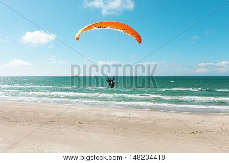 Paragliding on the deserted beach, unspoiled nature