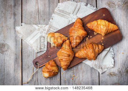 Food and drink, still life concept. Fresh croissants for breakfast on a rustic wooden table. Selective focus, top view overhead flat lay