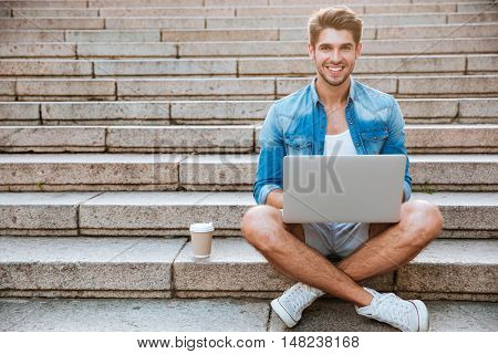 Young casual smiling man student using laptop while sitting on the staircase outdoors with cup of coffee