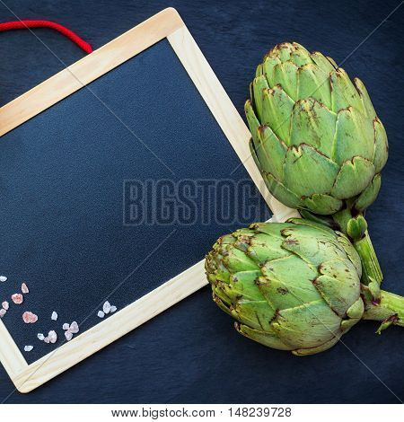 Organic fresh artichokes with copy space board, grunge moody background. Selective focus, top view overhead flat lay