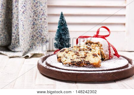 German stollen pie on a wooden background with sugar powder selective focus