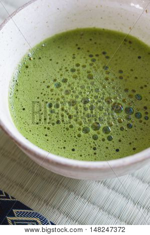 Japanese Matcha green tea in a chawan or traditional ceramic bowl shot with shallow focus