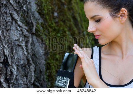 Female Runner Pushing Smart Phone In Sport Armband