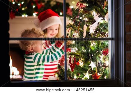 Happy little kids in matching red and green striped pajamas decorate Christmas tree in beautiful living room with traditional fire place. Children opening presents on Xmas eve. View though window.