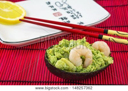 Tasty avocado salad with two shrimps, lemon and red chopsticks lies on the white plate