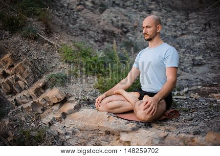 Man meditating in the mountain in the morning. Doing yoga outdoors on the cliff. Relaxation and healthy lifestyle