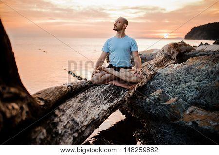 Man meditating on broken tree near sea on sunset . Doing yoga outdoors. beautiful background