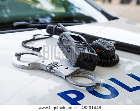 Police equipment on a  police car.  Handcuffs, baton and pager on top of a police car. Selective focus