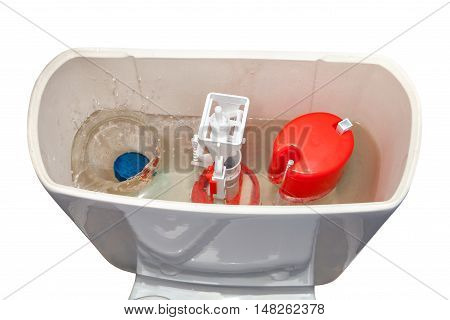 Blue cleaner water soluble tablet falls into toilet flush tank isolated on white background.