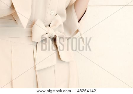 details of bow belt tie in beige woman dress outfit style.