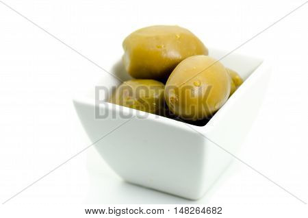 Kalamata green olives with water drops in white small bowl isolated on white
