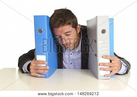 young attractive busy businessman overwhelmed suffering crazy stress at office exhausted and helpless holding paperwork folders napping on desk in business frustration and overwork problem