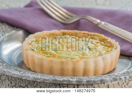 Serving of quiche florentine which is made of eggs cream spinach and cheese.