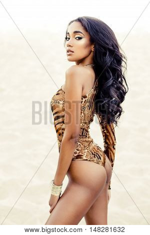 Attractive African-American girl in swimwear on sandy beach poster