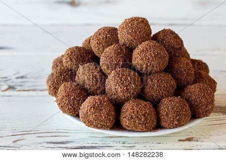 Pile of candies on plate. Brown sweets with crumbs. Simple recipe of chocolate balls. Cocoa and crumbled cookies.